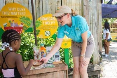 A volunteer at ZooTampa helps a young girl