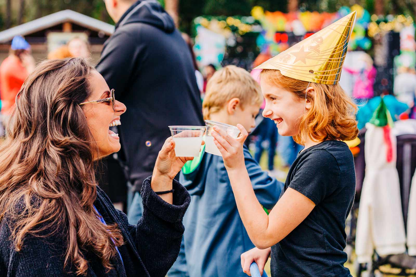 A young girl wearing a party hat toasts with her mom with a glass of lemonade at Noon Year's Eve at ZooTampa on December 31st while bubbles lift past them into the air