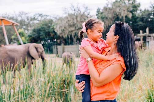 A mom holds her daughter as they watch the elephants and other African animal wildlife at ZooTampa