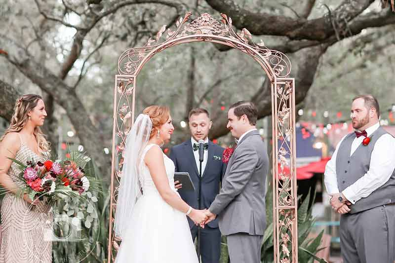 A couple getting married under a golden arch and big trees at the Zoo in Tampa