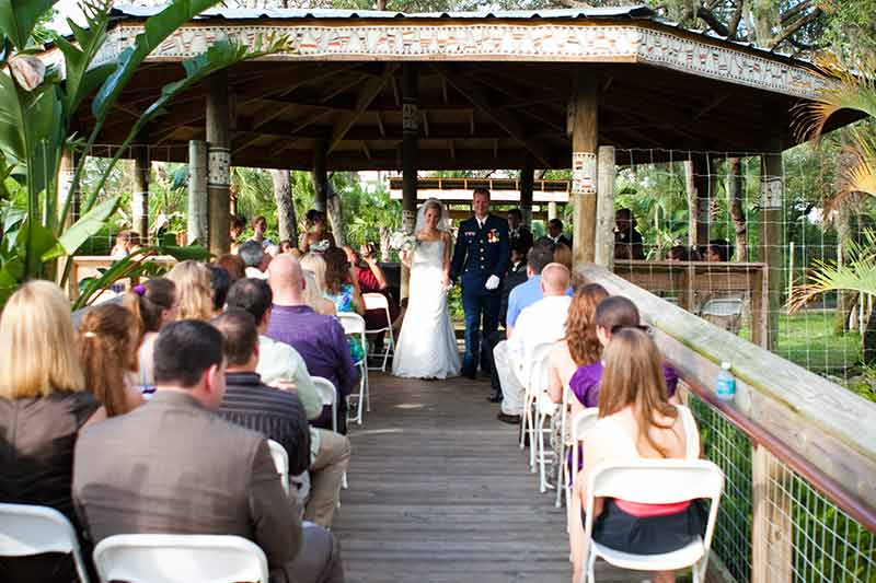 Bride and groom walk down the aisle outside during their wedding ceremony at Ituri Forest at the Zoo in Tampa