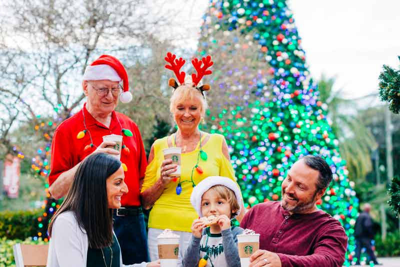 A family enjoys holiday treats while they gather by the huge Christmas tree at ZooTampa